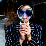 Person holding up a magnifying glass to face